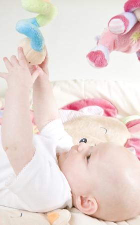 defenseless: baby girl lying down on playing mat Stock Photo