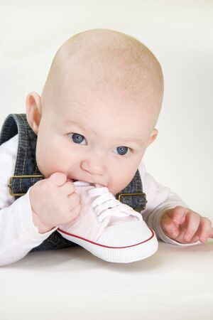 defenseless: portrait of lying down baby girl holding a shoe