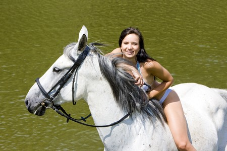 equestrian on horseback riding through water photo