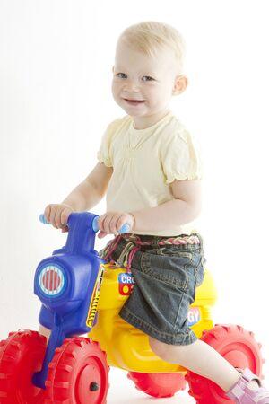 little girl on toy motorcycle photo