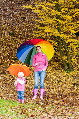 mother and her daughter with umbrellas in autumnal nature photo