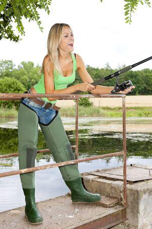 fisherwoman: woman fishing at pond