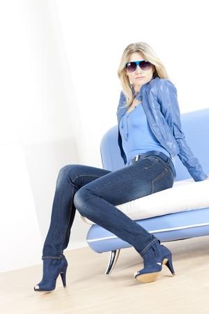denim jacket: woman wearing blue clothes sitting on sofa
