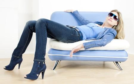 denim jacket: woman wearing blue clothes lying on sofa Stock Photo