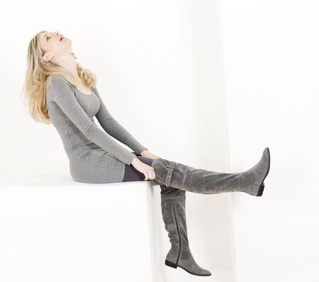 women in boots: sitting woman wearing fashionable gray boots