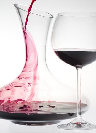 Glas Wein und Karaffe mit Rotwein