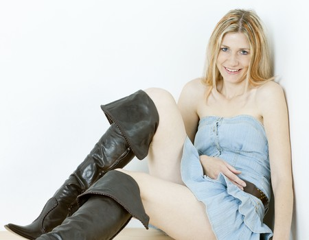 women in boots: sitting woman wearing fashionable brown boots