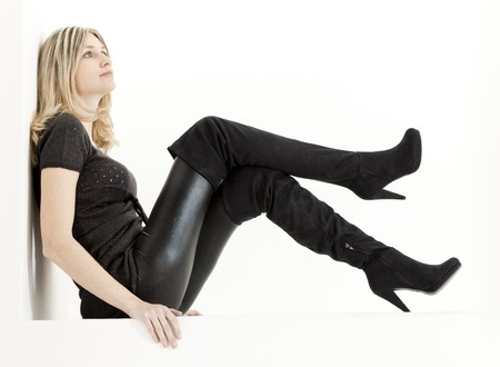 women in boots: sitting woman wearing fashionable black boots