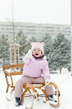 little girl sledding in snow photo