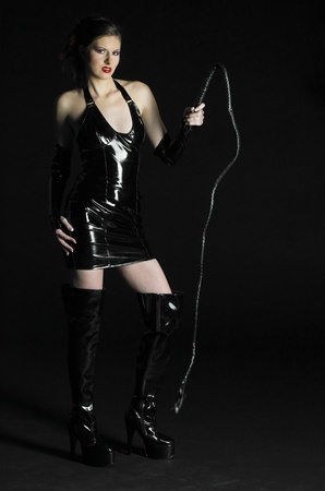 domina: woman in latex with whip Stock Photo