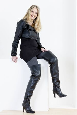 sitting pregnant woman wearing fashionable black boots photo