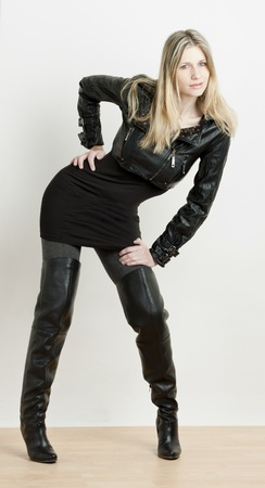 standing woman wearing fashionable black boots photo