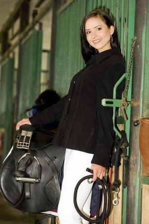 dark haired woman: equestrian with saddle in a stable