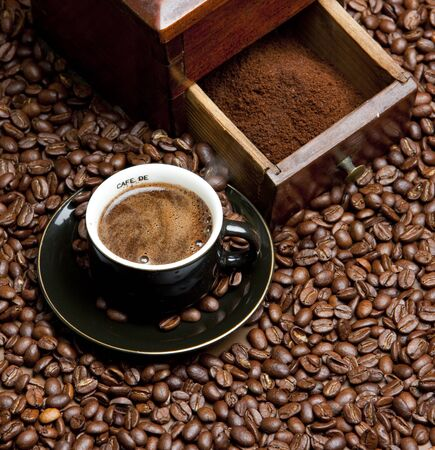 bodegones: detalle de la f�brica de caf� con granos de caf� y la taza de caf� Foto de archivo