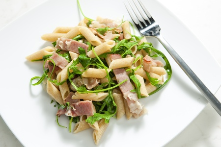 ruccola: penne pasta with Parma ham and ruccola Stock Photo