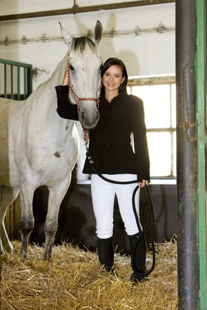 equestrian with horse in stable photo