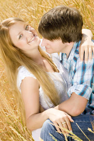 young couple sitting in grain field Stock Photo - 9619901