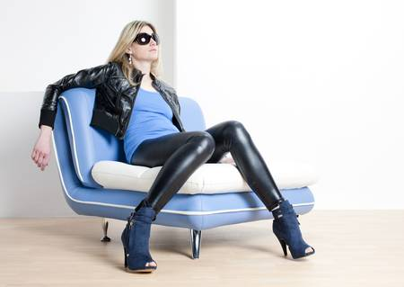 woman wearing fashionable shoes sitting on sofa photo