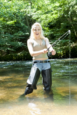women in boots: woman fishing in river