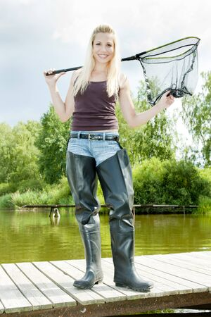 fisherwoman: fishing woman with landing net standing on pier Stock Photo