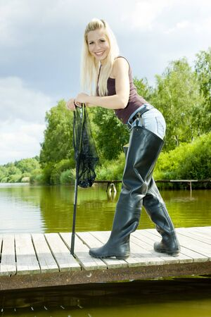 fishing woman with landing net standing on pier photo