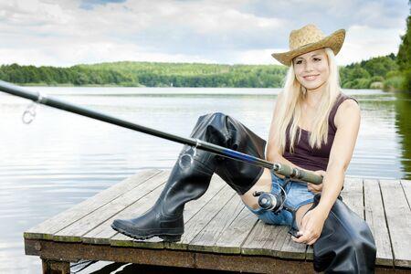 fishing woman sitting on pier photo