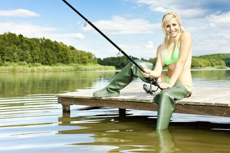 blonde bikini: fishing woman sitting on pier Stock Photo