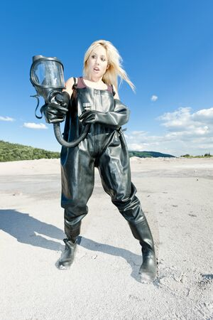 standing woman with gas mask wearing protective clothes photo
