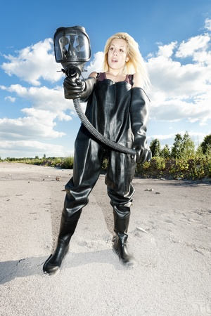 standing woman with gas mask wearing protective clothes Stock Photo