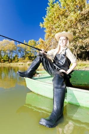 fishing woman sitting on boat photo