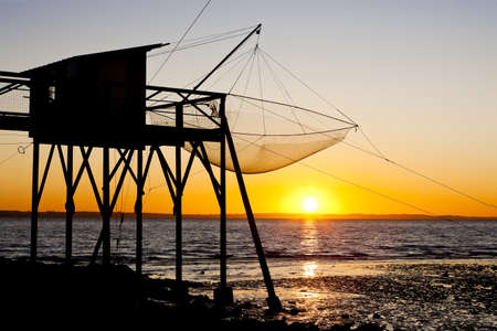 auroral: pier with fishing net during sunrise, Gironde Department, Aquitaine, France Stock Photo