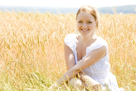 portrait of woman sitting in grain field photo