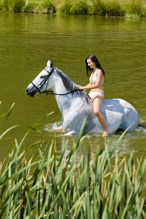 dark haired woman: equestrian on horseback riding through water
