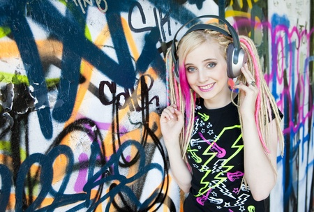 portrait of young woman with headphones at graffitti wall photo