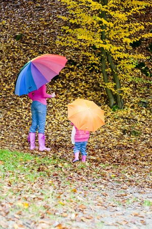 falltime: mother and her daughter with umbrellas in autumnal nature