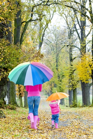 woman with umbrella: mother and her daughter with umbrellas in autumnal alley