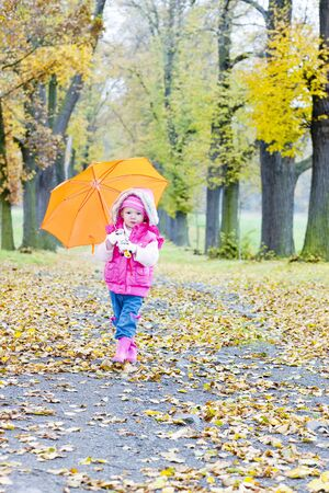 falltime: little girl with umbrella in autumnal alley Stock Photo