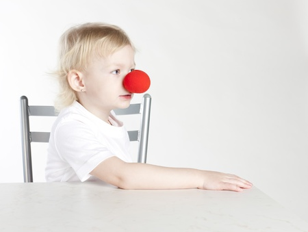 portrait of little girl with a clown nose photo