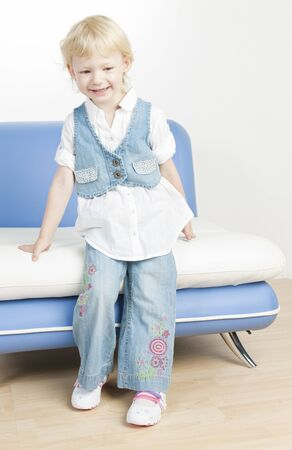 little girl standing by sofa photo