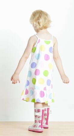 little girl wearing dress and rubber boots photo