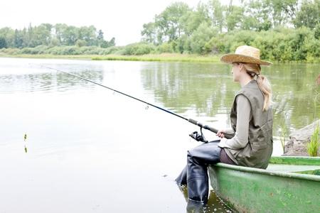 resting rod fishing: fishing woman sitting on boat