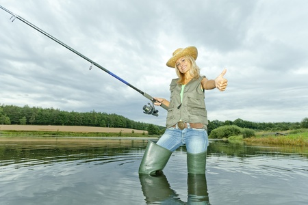 resting rod fishing: woman fishing in pond Stock Photo