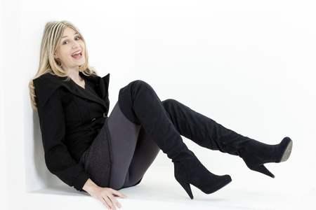 zittende vrouw, gekleed in modieuze zwarte laarzen
