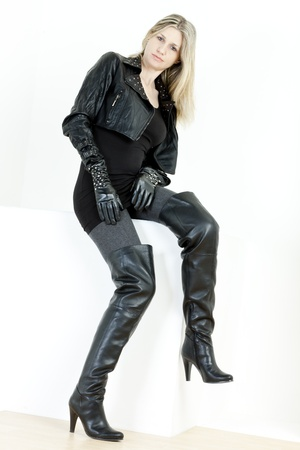 sitting woman wearing fashionable black boots photo