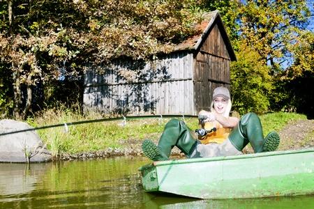 fisherwoman: fishing woman sitting on boat