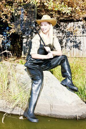 fisherwoman: fisher woman with landing net sitting on stone