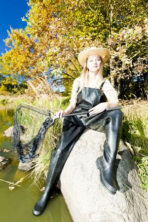 fisher woman with landing net sitting on stone photo