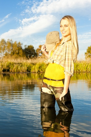 fisherwoman: fisher woman standing in pond Stock Photo