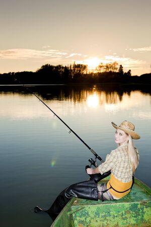 une femme assise sur la pêche en bateau
