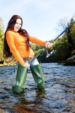 woman fishing in Otava river, Czech Republic photo